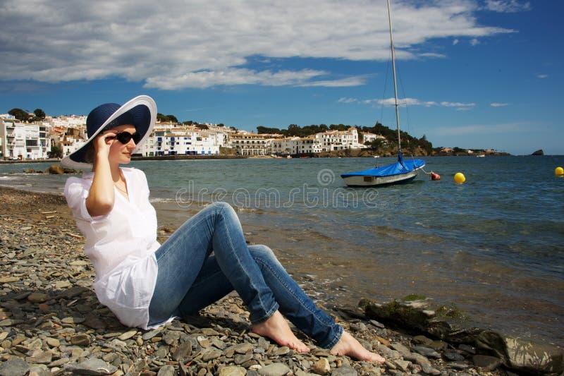 Frau im Hut, der auf einem Strand sitzt stockbilder