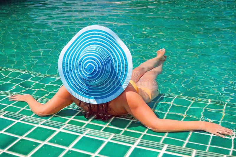 Frau im Hut, der am Swimmingpool sich entspannt stockbilder