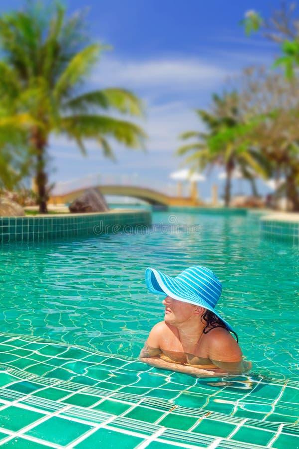 Frau im Hut, der am Swimmingpool sich entspannt lizenzfreies stockbild