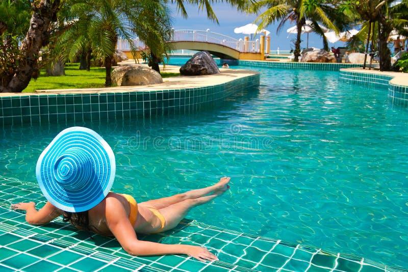 Frau im Hut, der am tropischen Swimmingpool sich entspannt lizenzfreie stockbilder