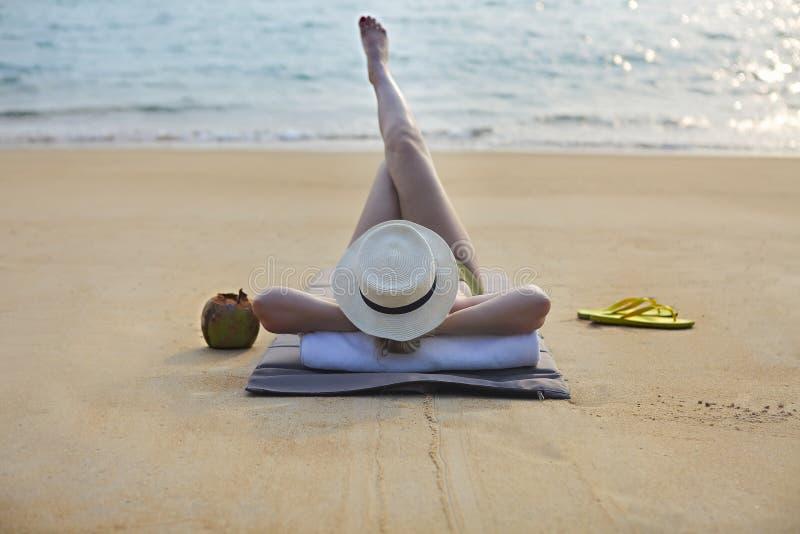 Frau im Hut mit Kokosnusscocktail auf dem Strand stockbild