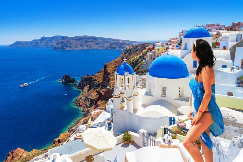 Frau im Hut an schöner Oia-Stadt von Santorini-Insel in Griechenland lizenzfreie stockbilder