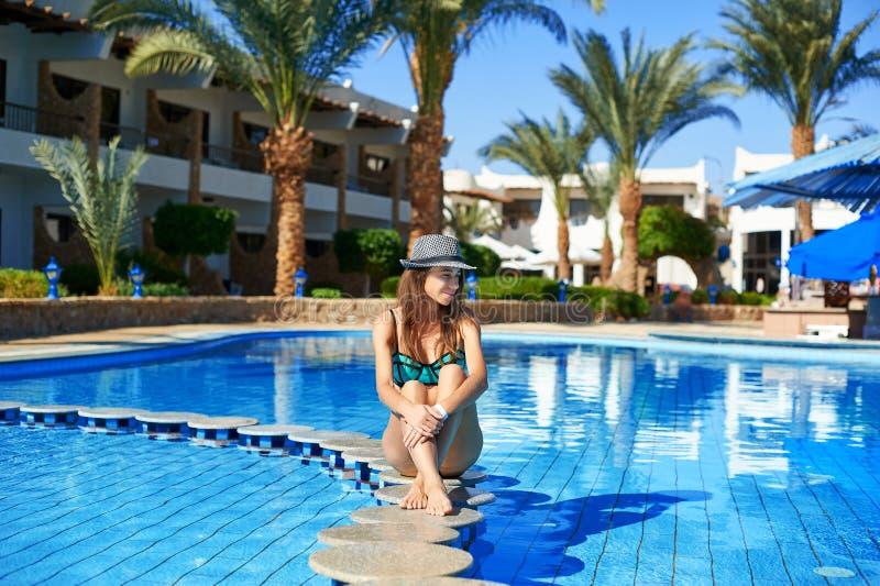 Frau im Hut sitzt am Rand des Steins mitten in dem Swimmingpoolbadekurort Schönes exotisches Hotel sich entspannen stockfotografie