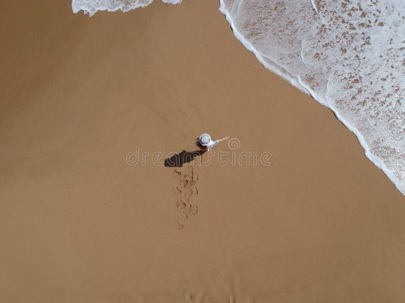 Frau im Hut am tropischen Strand mit Meereswogen über Ansicht lizenzfreies stockfoto