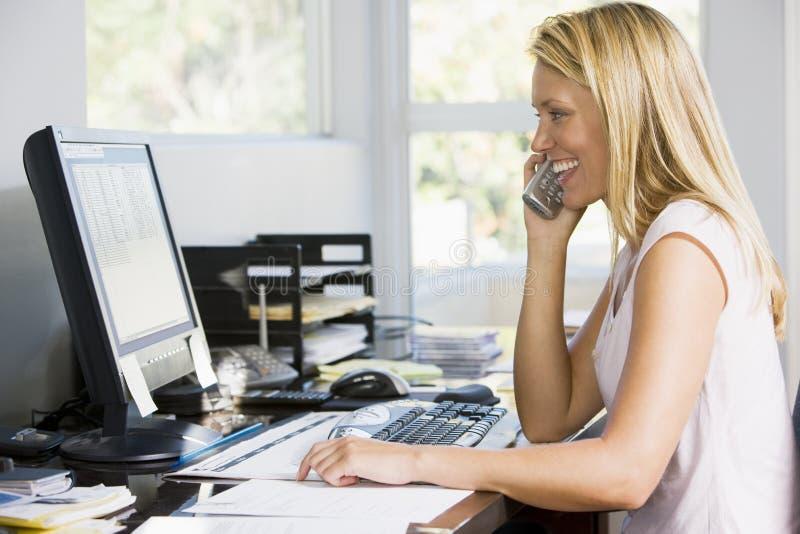 Frau im Innenministerium mit Computer unter Verwendung des Telefons lizenzfreies stockfoto