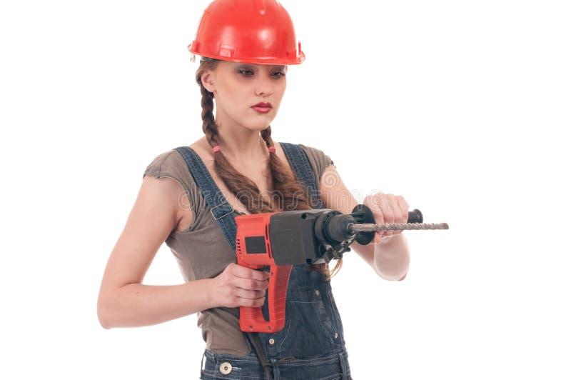 Frau im Jeansoverallholding-Perforatorbohrgerät stockfoto