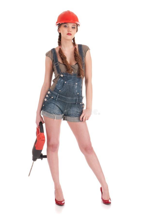 Frau im Jeansoverallholding-Perforatorbohrgerät lizenzfreie stockfotografie