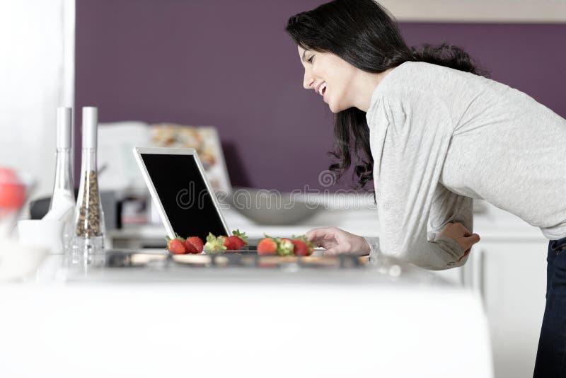 Frau im Küchenleserezept stockfotografie