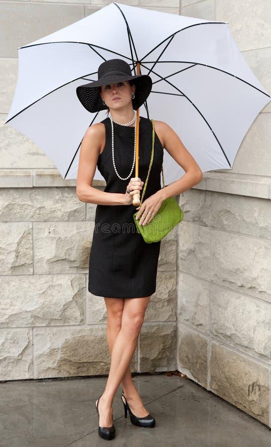 Frau im klassischen schwarzen Kleid mit weißem Regenschirm lizenzfreie stockfotos