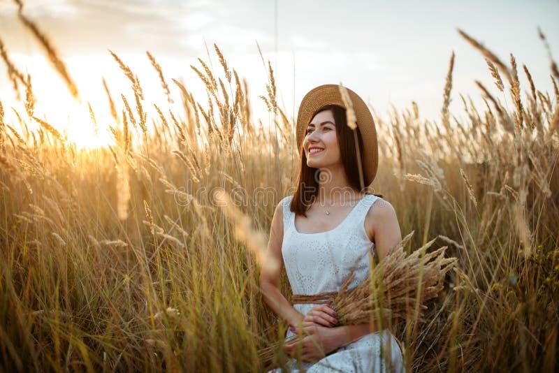 Frau im Kleid und im Strohhut hält Weizenblumenstrauß lizenzfreies stockbild