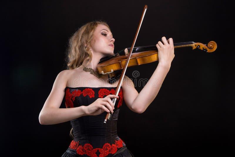 Frau im Kleid, welches die Geige spielt stockbild