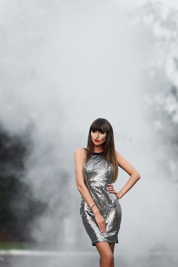 Frau im kurzen grauen glänzenden Kleid, das auf Rauche aufwirft stockfoto