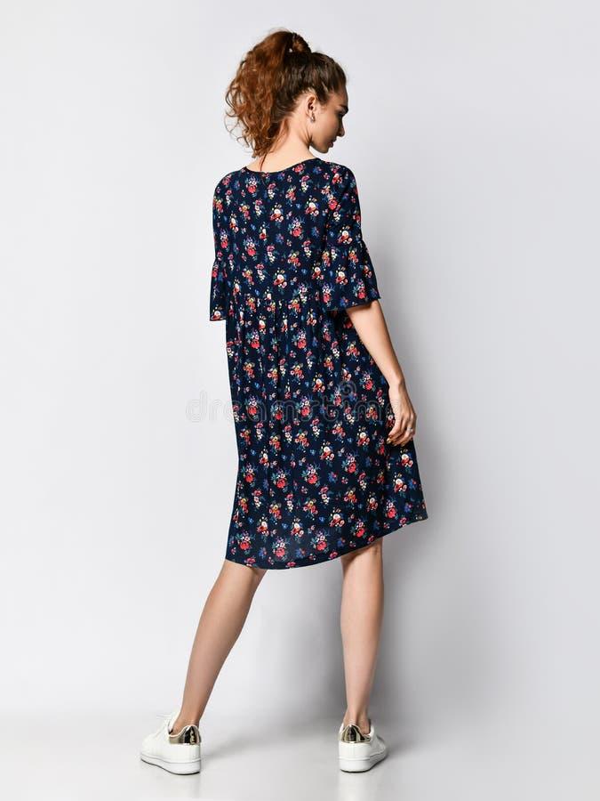 Frau im langen Blumenkleiderin mode Speicher - Portr?t des M?dchens in einem Kleidungsgesch?ft in einem Maxi Sommerkleid lizenzfreie stockfotografie