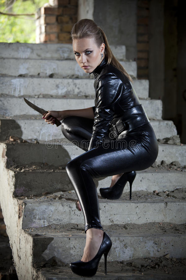 Frau im ledernen Kleid und im Kampfmesser stockbild
