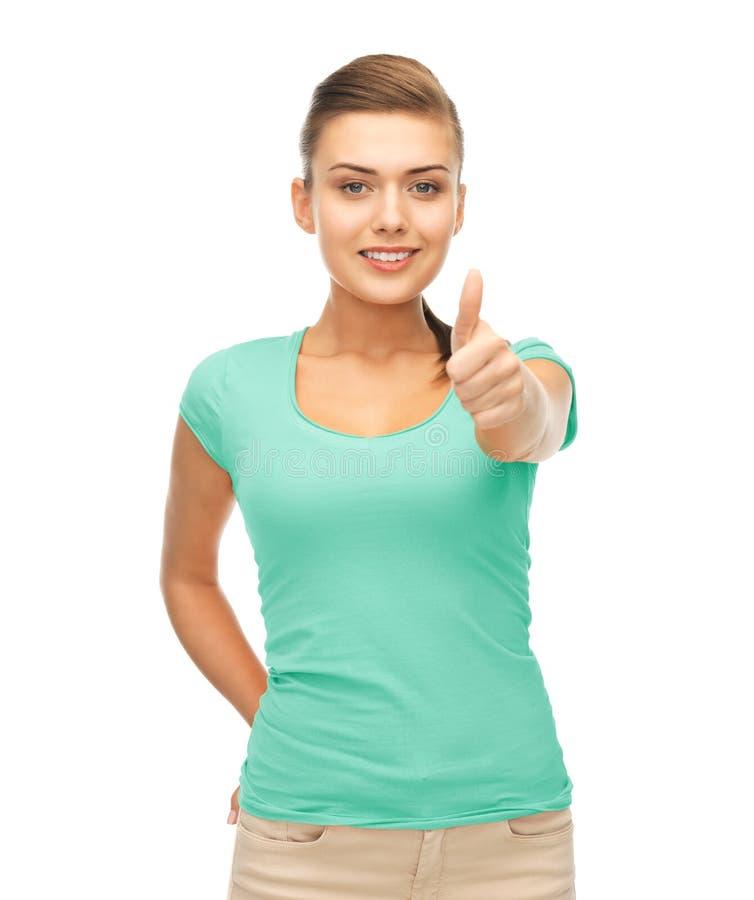 Frau im leeren blauen T-Shirt, das sich Daumen zeigt stockbild