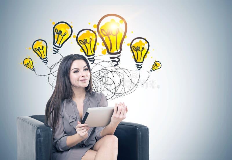 Frau im Lehnsessel, eine Tablette, gute Ideen lizenzfreies stockbild