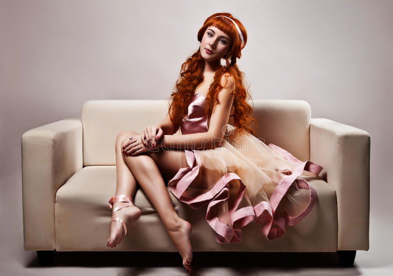 Frau im luxuriösen Kleid, das auf Sofa sitzt stockfotos