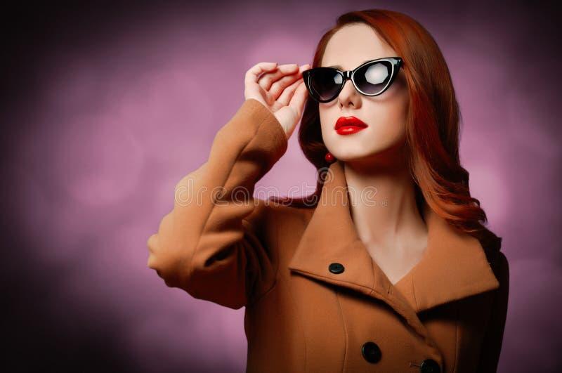 Frau im Mantel und in der Sonnenbrille auf purpurrotem Hintergrund stockbilder