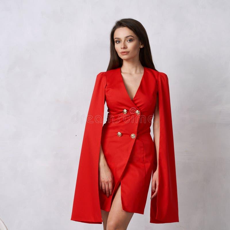 Frau im mini roten Kleid mit goldenen Knöpfen und hängenden Ärmeln lizenzfreies stockfoto
