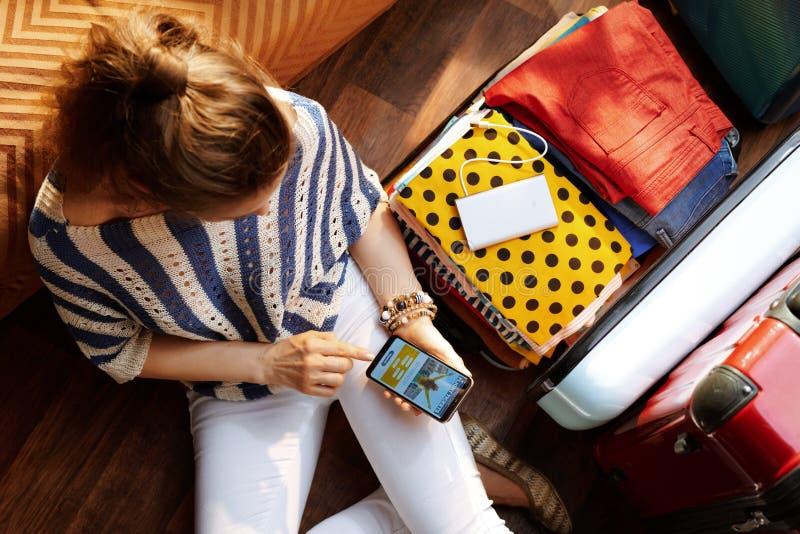 Frau im modernen Haus im sonnigen Sommerkassabuchflug am Telefon lizenzfreie stockfotografie