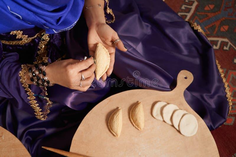 Frau im Nationalkostüm, bereitet traditionelles Shekerbura-Gebäck zu stockfotografie