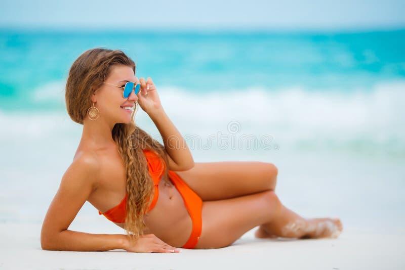 Frau im orange Bikini auf einem tropischen Strand stockbilder