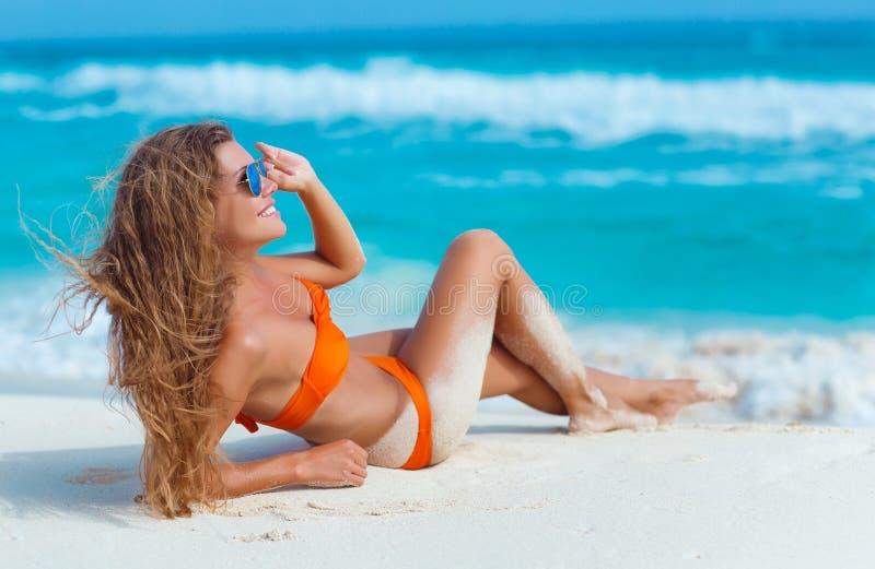 Frau im orange Bikini auf einem tropischen Strand stockbild