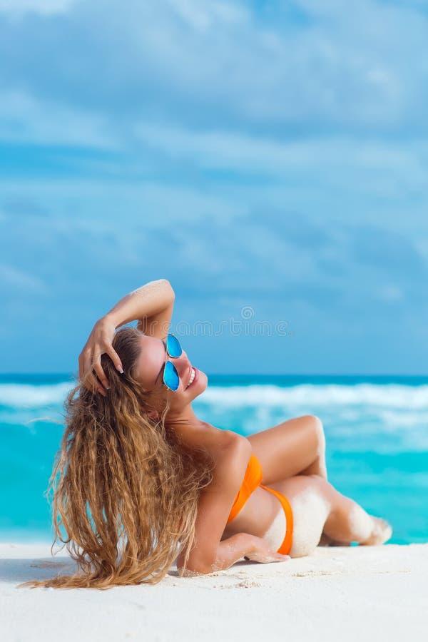 Frau im orange Bikini auf einem tropischen Strand lizenzfreies stockbild