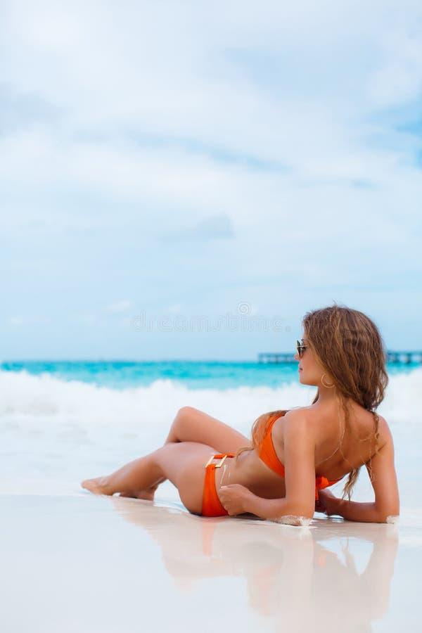 Frau im orange Bikini auf einem tropischen Strand lizenzfreie stockbilder