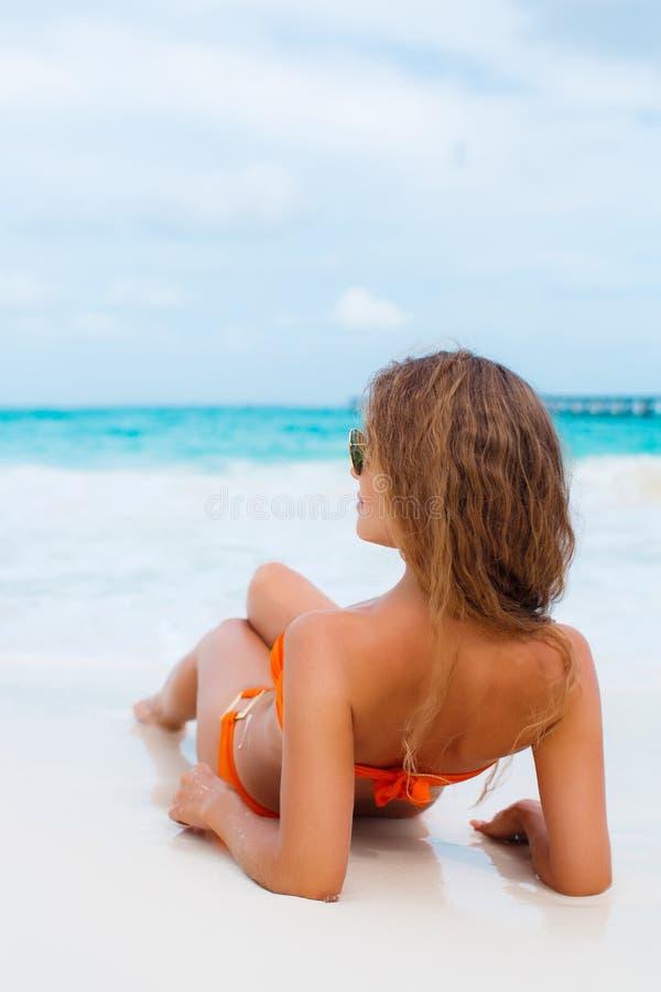 Frau im orange Bikini auf einem tropischen Strand stockfotos
