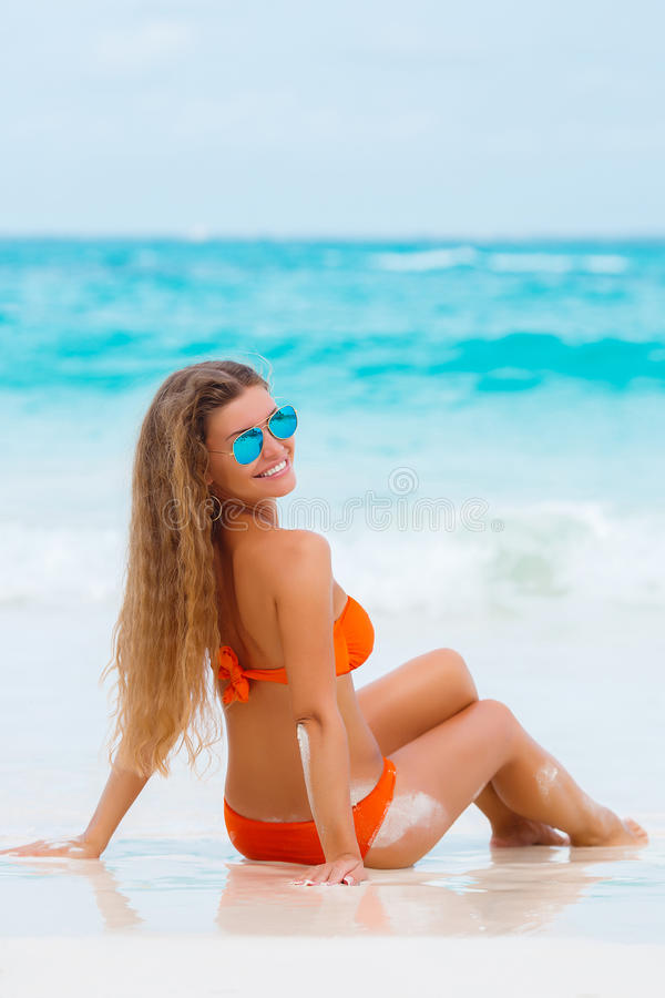 Frau im orange Bikini auf einem tropischen Strand stockfoto