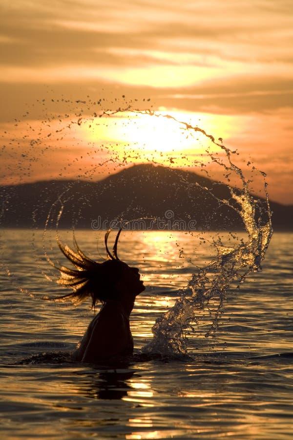 Frau im Ozean am Sonnenuntergang stockfotos