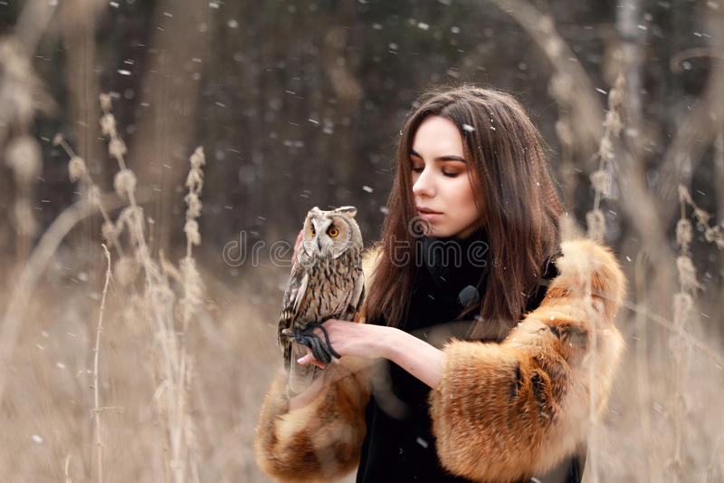 Frau im Pelzmantel mit Eule an Hand durch ersten Herbstschnee Beautif stockbild