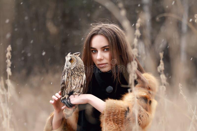 Frau im Pelzmantel mit Eule an Hand durch ersten Herbstschnee Beautif lizenzfreie stockfotografie