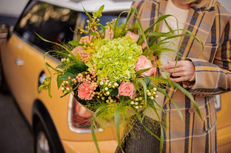 Frau im Plaidmantel mit einem schönen Blumenstrauß von Blumen gegen das gelbe Retro- Auto stockfoto
