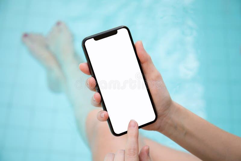 Frau im Pool, das Telefon mit einem lokalisierten Schirm hält stockfoto