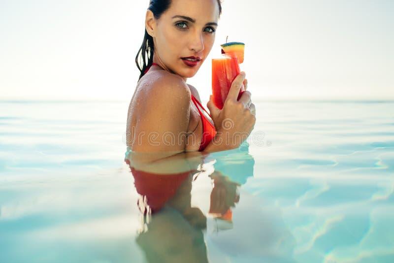 Frau im Pool mit Cocktail lizenzfreie stockfotos