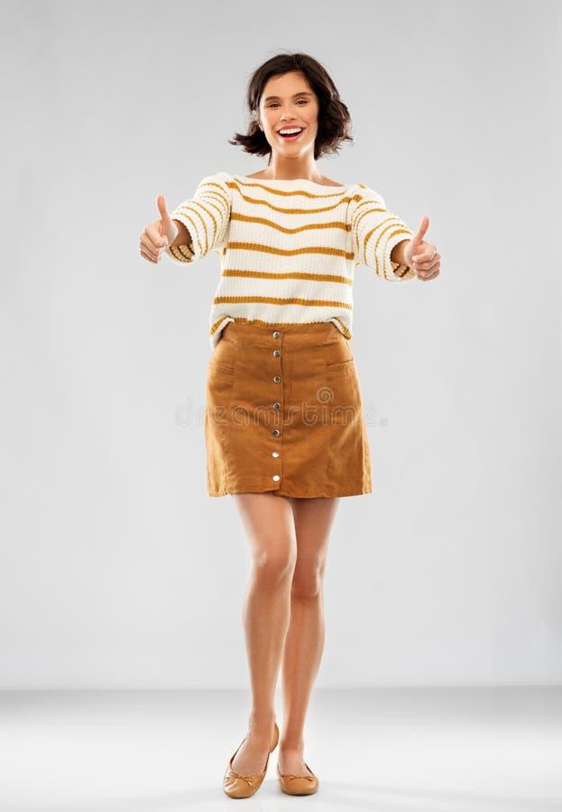 Frau im Pullover, im Rock und in den Schuhen zeigt sich Daumen stockfoto