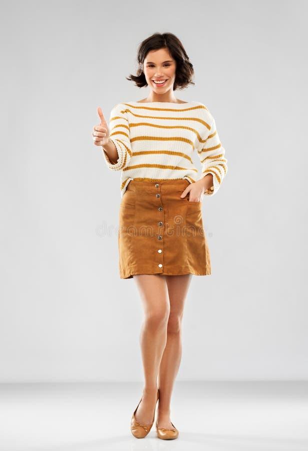 Frau im Pullover, im Rock und in den Schuhen zeigt sich Daumen stockbild
