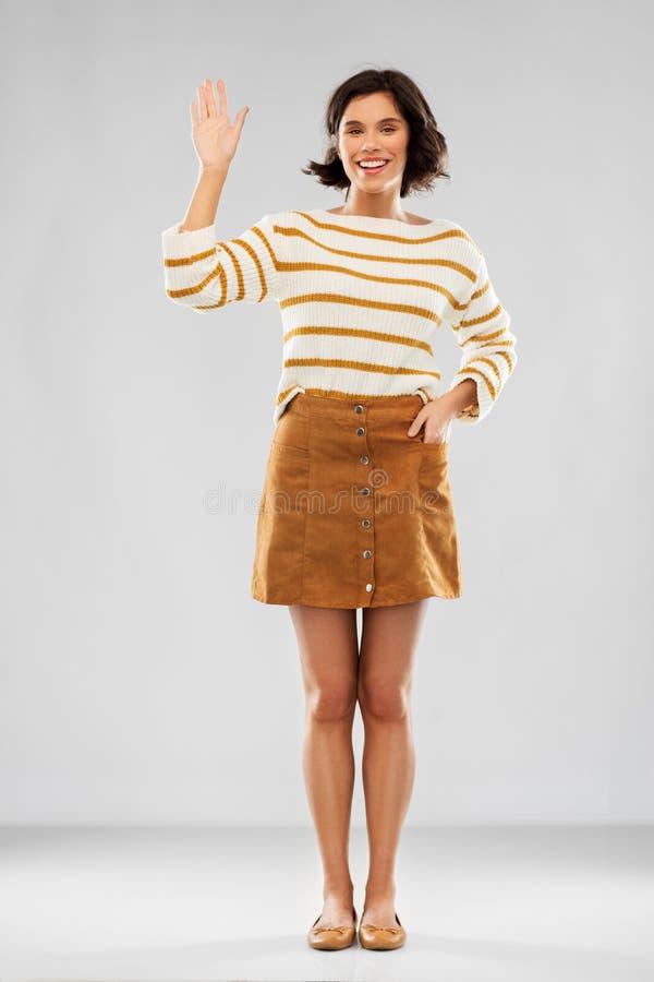 Frau im Pullover, in Rock und in Schuhen, die Hand wellenartig bewegen lizenzfreie stockfotos