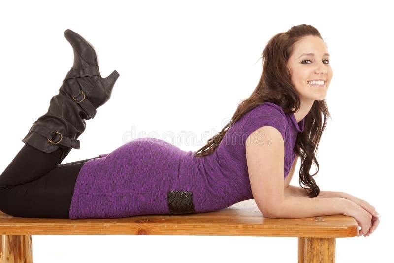 Frau im Purpur auf Magen auf Bank stockfotos