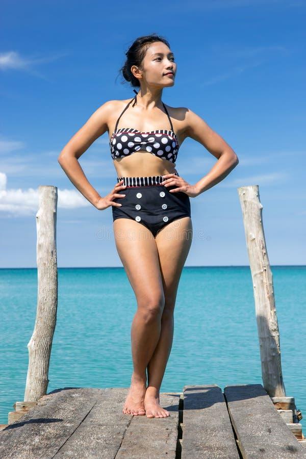 Frau im Retro- Badeanzug, der auf der Mole aufwirft lizenzfreie stockfotografie