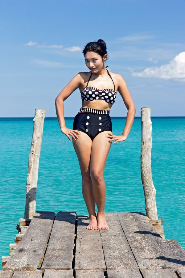 Frau im Retro- Badeanzug, der auf der Mole aufwirft stockbild
