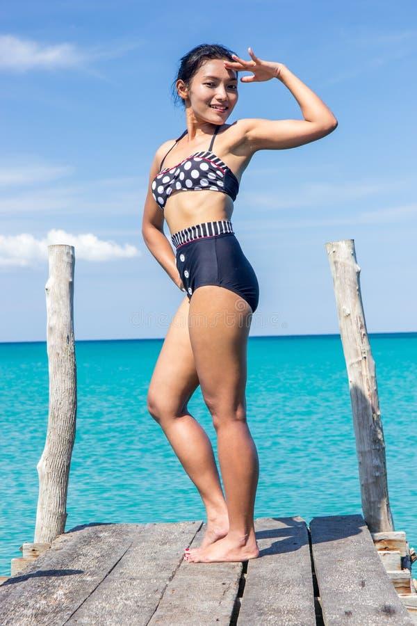 Frau im Retro- Badeanzuggruß auf dem Pier stockfotografie