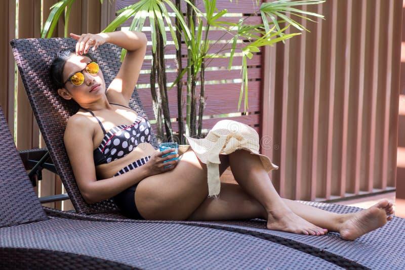 Frau im Retro- Bikini, der auf einem deckchair liegt lizenzfreies stockbild