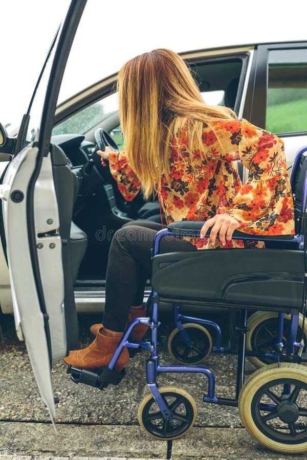 Frau im Rollstuhl, der in Auto einsteigt stockfoto