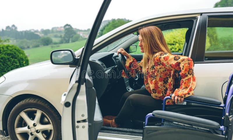 Frau im Rollstuhl, der das Auto verlässt lizenzfreies stockbild