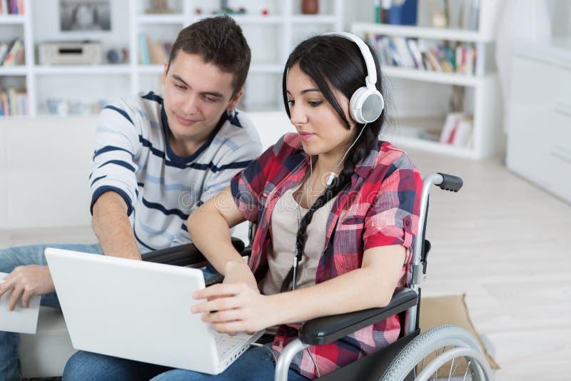 Frau im Rollstuhl mit dem Freundhelfen lizenzfreies stockbild