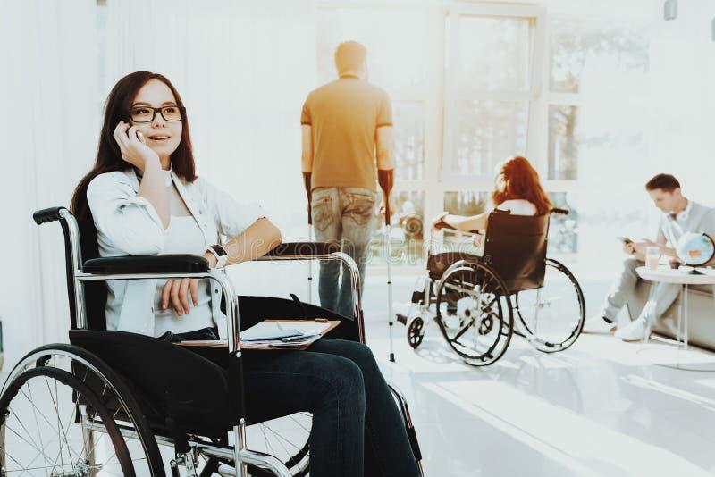 Frau im Rollstuhl spricht telefonisch am Flughafen stockfoto