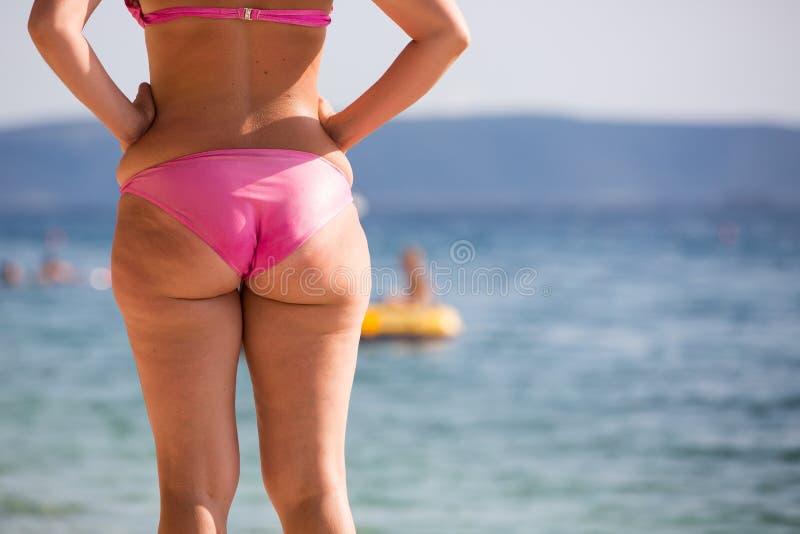 Frau im rosa Bikini an einem Strand stockfotografie